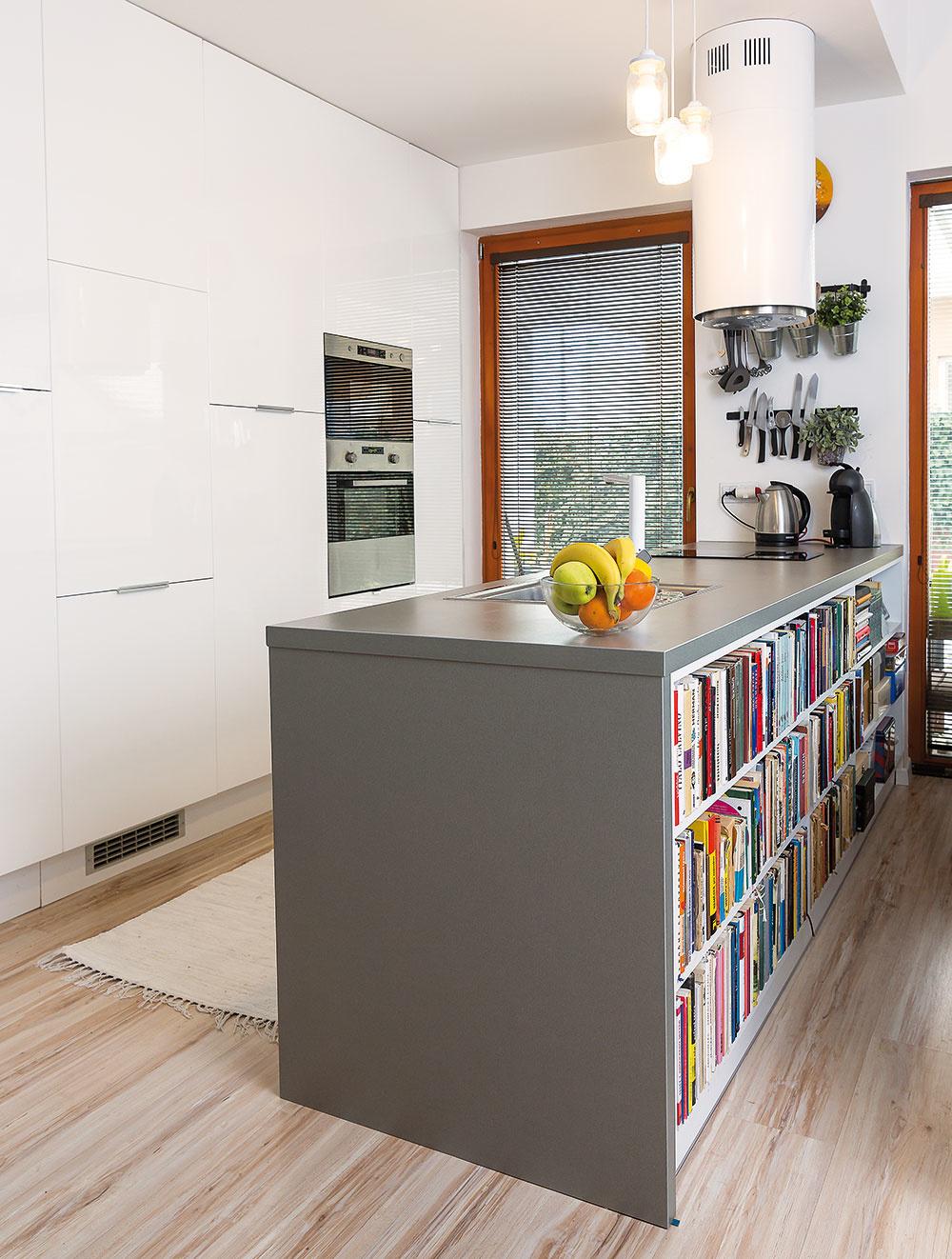Knihy uložené vkuchynskom ostrove zo strany obývačky podporujú prepojenosť týchto zón aumocňujú pocit kontinuity otvoreného denného priestoru.
