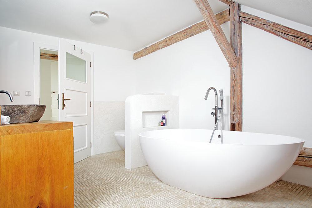 Voľne stojaca široká vaňa poskytuje obyvateľom dokonalý relax vo svetlom zaliatom podkrovnom priestore čistobielej kúpeľne, vktorej pekne vyniknú pôvodné drevené trámy.