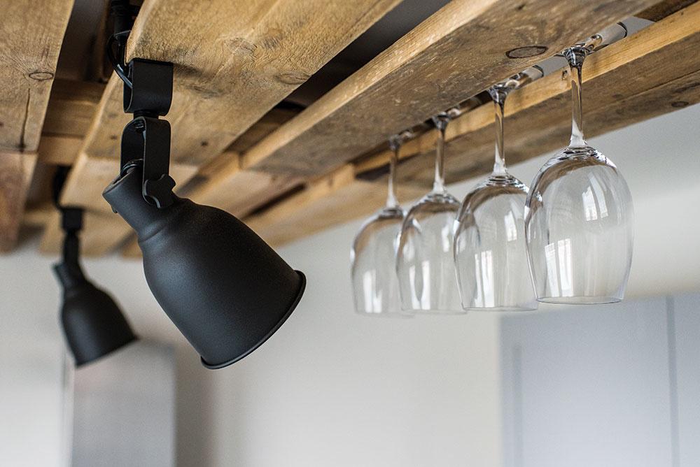 """Drevené palety efektne skryli nepekný spoj panelov na kuchynskom strope. """"Aj keď som strop vyrovnával, stále to nebolo ono. Nerovnosť bola príliš veľká,"""" vysvetľuje domáci pán. Tento nápad mal aj ďalšie výhody – na paletách sú upevnené lampy, pričom nebolo potrebné zasekávať prívodné káble,palety slúžia aj ako šikovný držiak na poháre."""