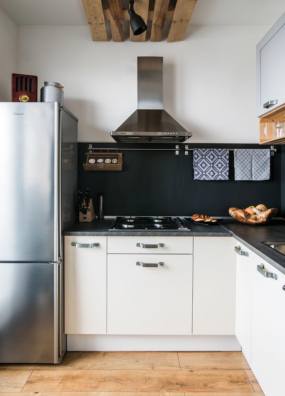Biele spodné skrinky kuchynskej linky sú jediným nábytkom, ktorý ostal vbyte zniekdajšieho zariadenia. Miro ich doplnil hornými strochu iným dezénom aj farbou avšetko prepojil čiernou pracovnou doskou azástenou. Kzladeniu prispeli aj originálne úchytky – pôvodným určením držadlá na debny.