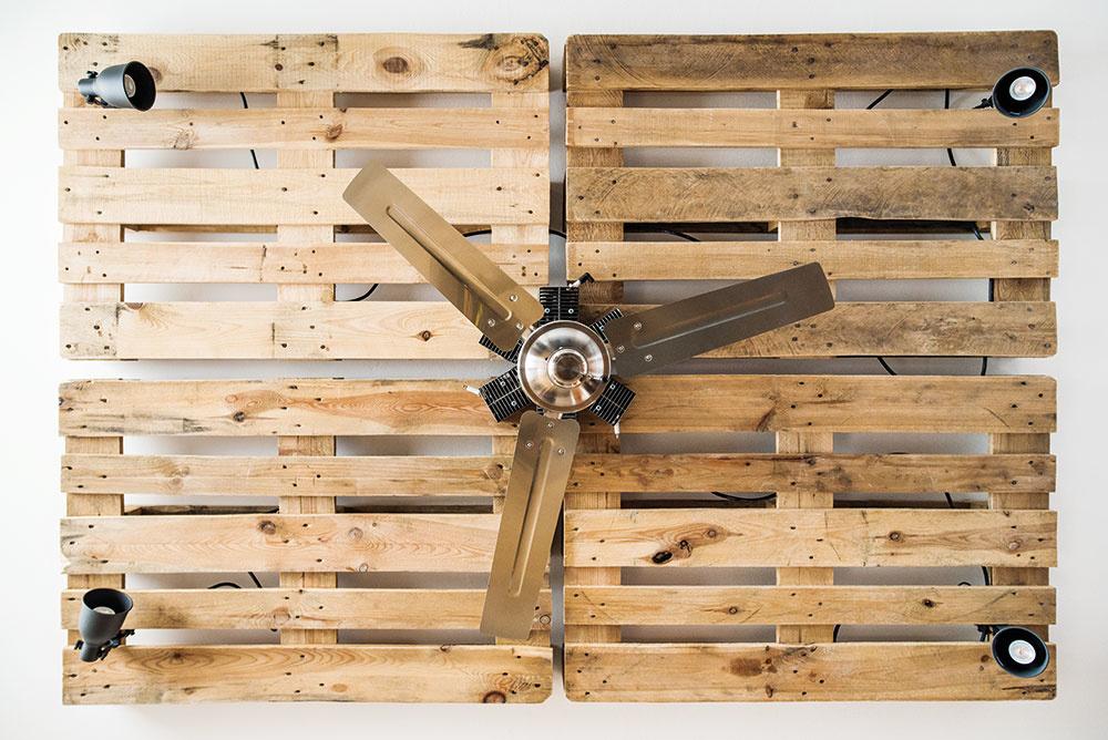 """Namiesto obvyklého lustra sú na strope obývačky palety so štyrmi smerovateľnými lampami v rohoch. Ventilátor uprostred (ako ináč, kúpený cez inzerát), tu vlete spríjemňuje klímu. """"Chcel som, aby pripomínal vrtuľu staréholietadla, preto sú okolo neho hlavy valcov zo stavebných strojov. Tieto súčiastky sa obvykle veľmi neničia, takže trvalo asi rok, kým som dal dokopy šesť vyradených kusov,"""" smeje sa domáci pán."""