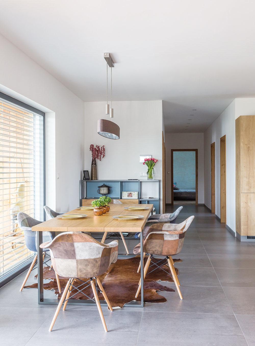 Jedálenskú časť tvoria masívny stôl apohodlné patchworkové kreslá. Nohy stolovníkov zahrieva kravská koža na podlahe azhora priestor opticky uzatvára podlhovasté stropné svietidlo. Všetko to pôsobí harmonicky aladí so zvyškom interiéru.