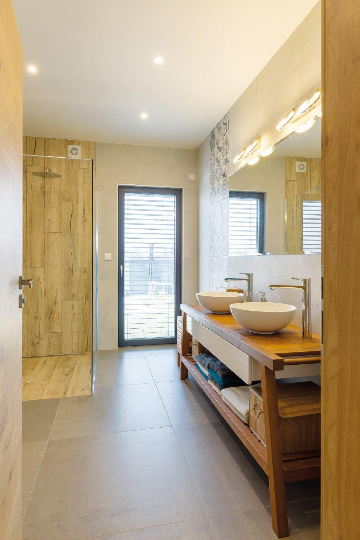 Voveľkoryso riešenej kúpeľni je otvorený sprchovací kút, obložený dlažbou imitujúcou drevo, čo pôsobí mimoriadne teplo aútulne.