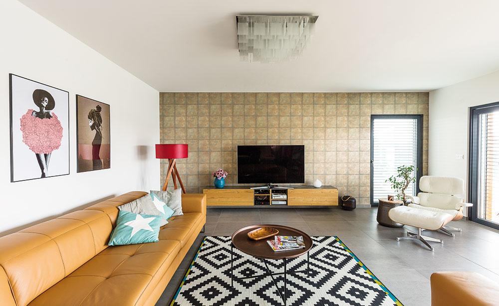"""Vkaždej miestnosti domu je tapeta, ktorá podčiarkuje atmosféru daného priestoru. Vobývacej izbe je industriálne pôsobiaca tapeta s3D efektom. Stena na prvý pohľad pôsobí, akoby na nej boli pribité malé plechové štvorce. Nejeden návštevník si ju ide rovno """"chytiť"""" azistiť, či je to skutočný plech."""