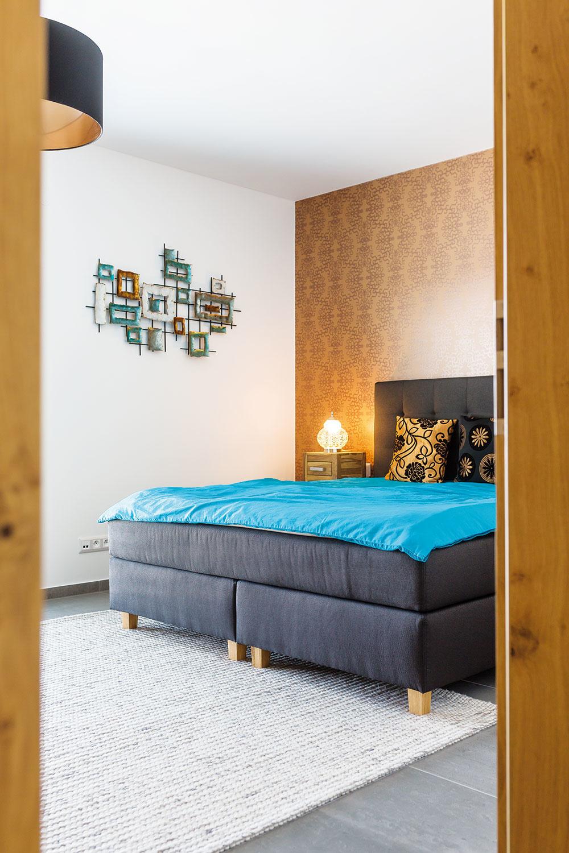 Vspálni sa oproti vstavaným skriniam smnožstvom úložného priestoru nachádza veľká čalúnená posteľ. Tapeta na stene za ňou priestor zútulňuje arovnako ako koberec ho pocitovo prehrieva. Nič iné okrem dvoch nočných stolíkov tam už nenájdete. Čistota afunkčná strohosť zariadenia sa nesie celým domom.