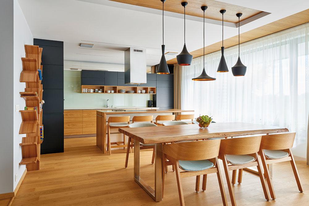 Vjedálenskej časti púta pozornosť masívny agátový stôl sprirodzene tvarovanými neopracovanými hranami vspoločnosti dizajnových stoličiek značky Ton.