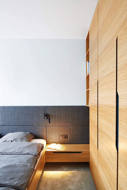 Vspálni rodičov sú posteľ aj vstavaná šatníková skriňa navrhnuté na mieru. Krásnu štruktúru prírodného dreva podčiarkujú tmavosivé textílie.