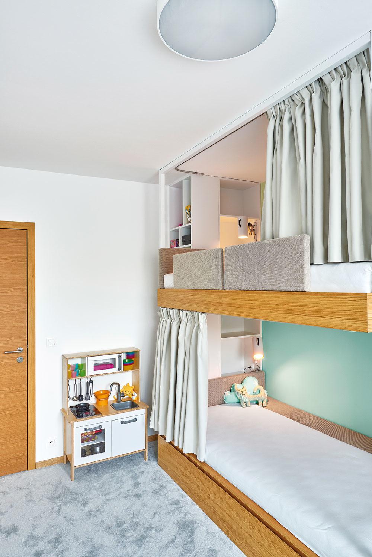Poschodová posteľ vdetskej izbe bola jednou zpožiadaviek domácich. Práve to umožnilo vytvoriť väčšiu plochu nahranie. Každé zlôžok pritom ponúka svojmu obyvateľovi dokonalé zázemie sodkladacím priestorom aosvetlením.