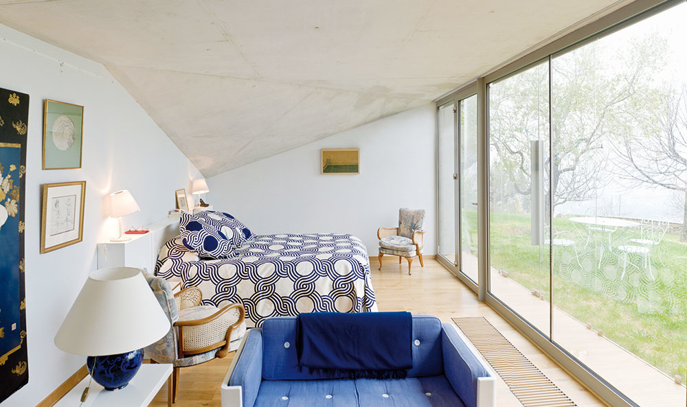Vspálni je betónový strop skosený. Strecha totiž sleduje líniu svahu azároveň vytvára jednu ztroch navzájom sa pretínajúcich plôch nadzemnej časti prístavby.