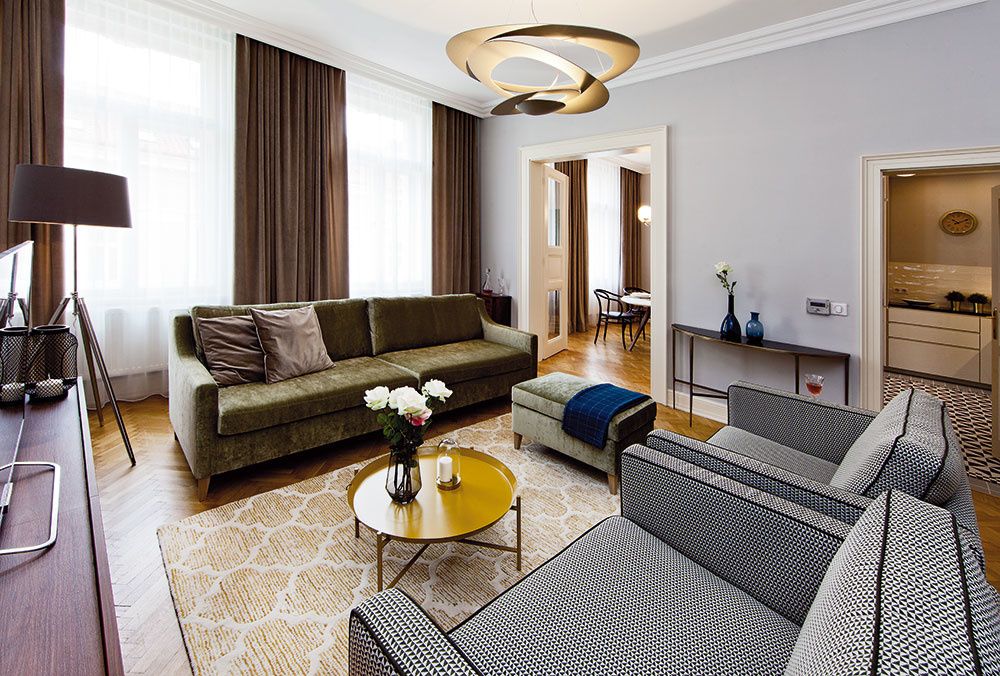 Eleganciu vnáša do obývačky aj klasický zamat, ktorý sa objavuje na zelenkavej pohovke spodnožkou aj na dlhých závesoch. Geometrický vzor poťahov na kreslách zas korešponduje sčierno-bielou podlahou vkuchyni.