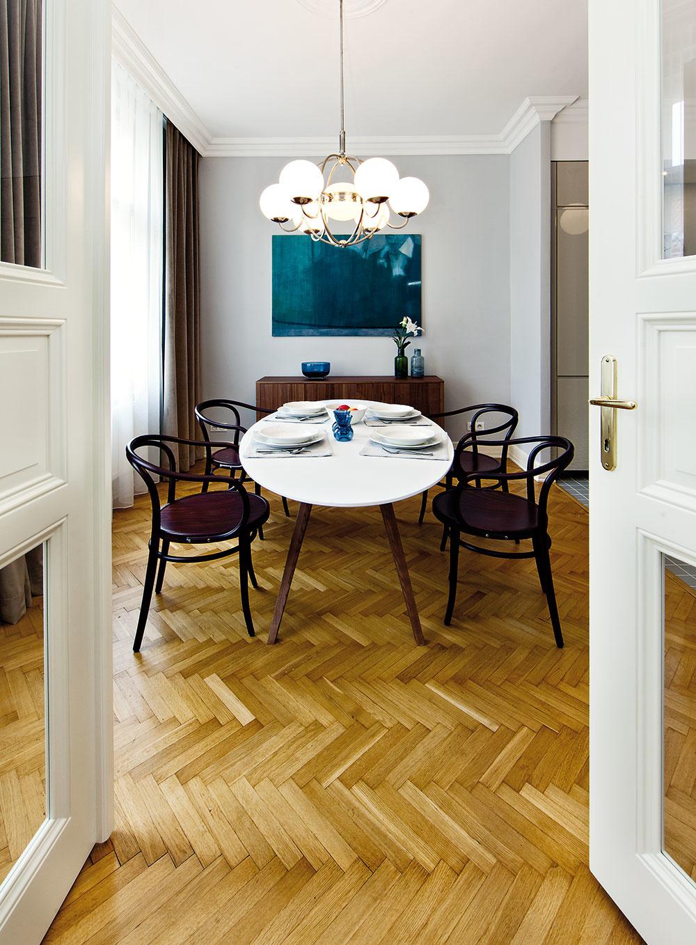 """Jedálenský stôl je doplnený novými stoličkami od českej značky TON. Zvlášť pyšná je architektka na starožitnú lampu nad ním. """"Po úmornom niekoľkomesačnom chodení po starožitnostiach sme konečne zohnali krásnu lampu za rozumnú sumu,"""" hovorí. """"Bol to prvý úlovok do tohto bytu aveľmi som sa zneho tešila. Neskôr sa nám podarilo doladiť knej podobné svietidlá aj vchodbe avkuchyni."""""""