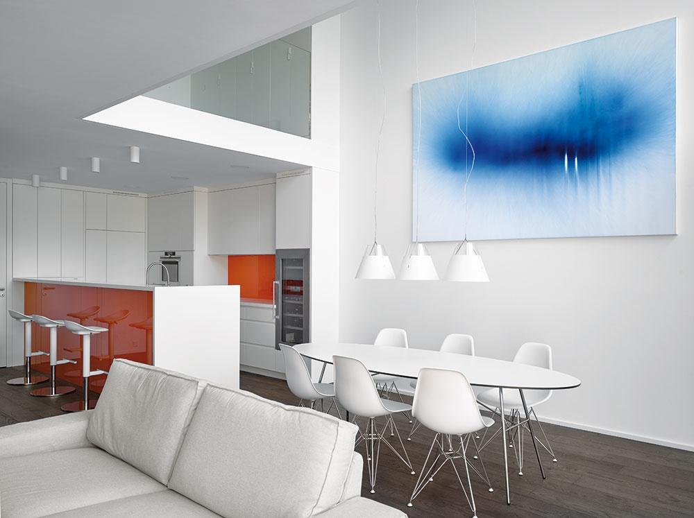 Interiéru dominuje biela farba, kontrastné sú len lesklé oranžové plochy na kuchynskej linke amodrý obraz.