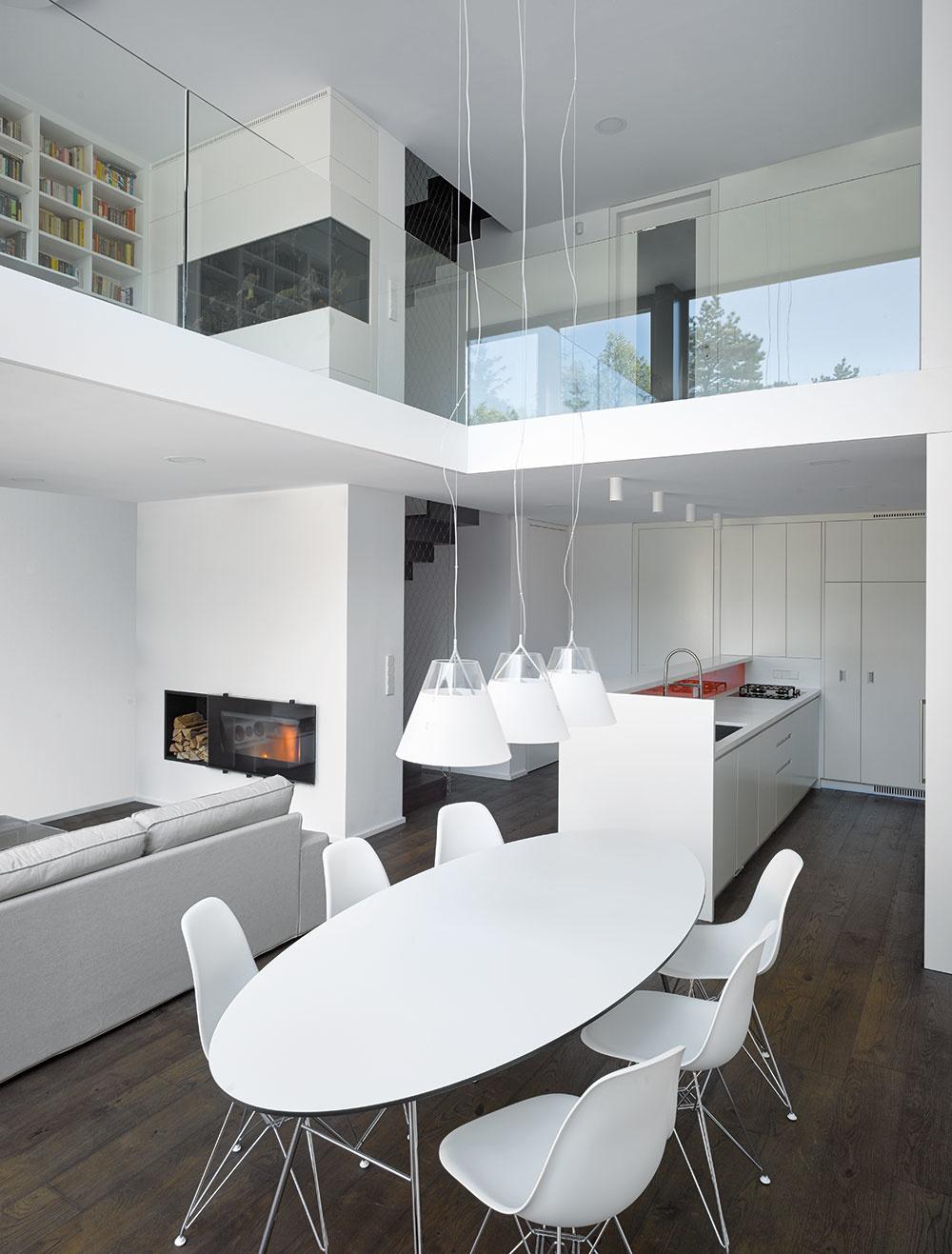 Oválny biely stôl stojí vcentre denného diania anarúša pravouhlé stereotypy opakujúce sa vinteriéri. Trojica visiacich lámp si cestu preráža cez dve poschodia, čím ešte väčšmi zdôrazňuje otvorený vertikálny priestor.