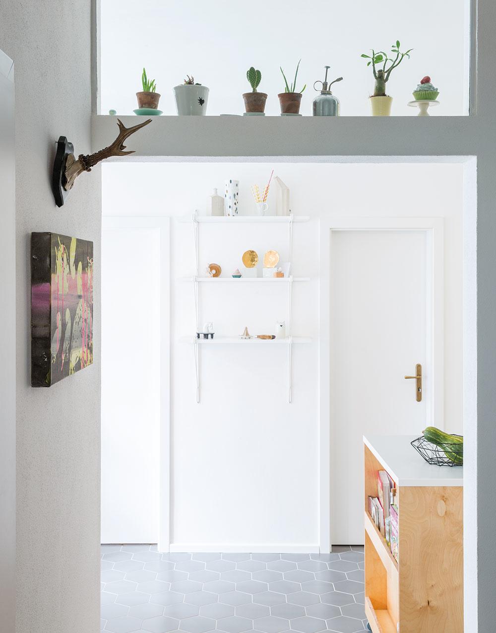 Votvorenom priehľade zobývacej izby do kuchyne dominuje biela farba smnožstvom izbových rastlín, ktoré tu majú výborné podmienky na svoj rast.
