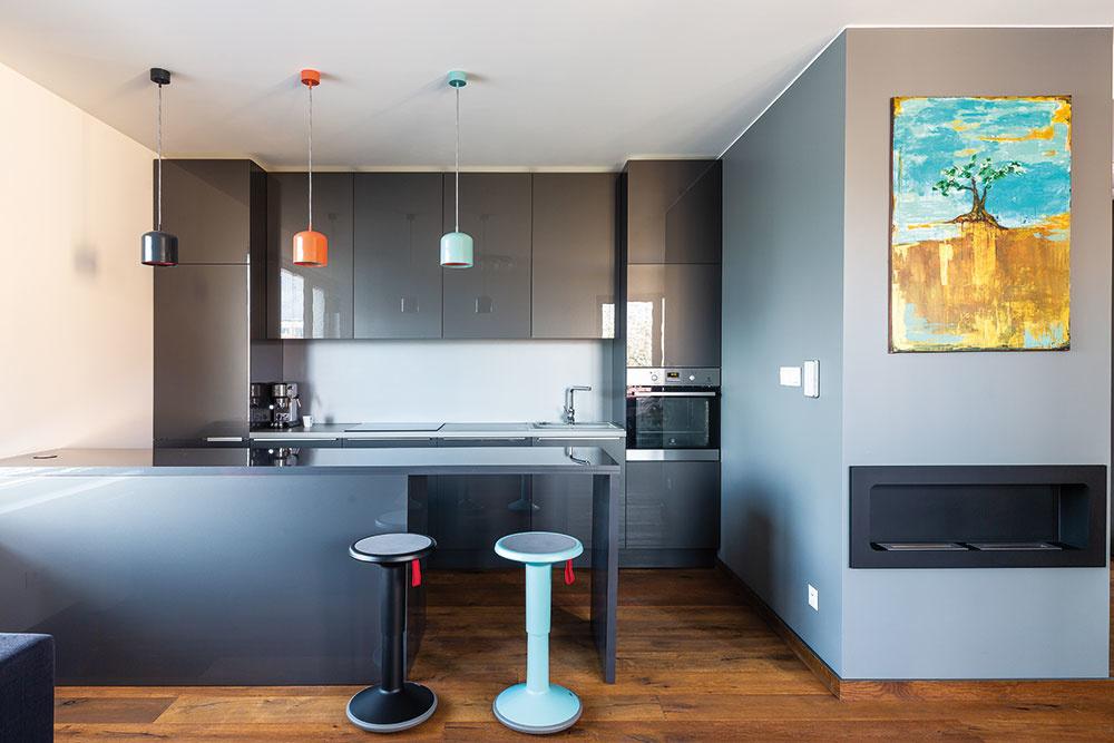 Chladnejší dojem zo sivej kuchynskej linky či niektorých na sivo natretých stien vyvažuje teplo pôsobiace drevo. Vbyte sa vďaka nemu cítite útulne.