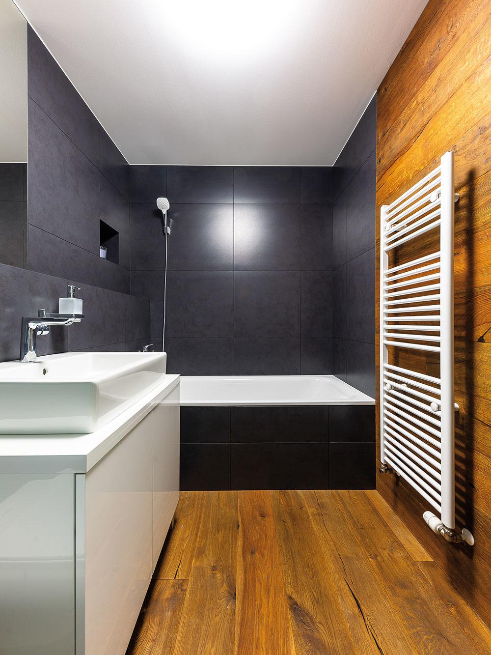 Trojfarebná kúpeľňa. Tmavý antracitový veľkoplošný obklad, čistá biela ateplé drevo. Majiteľ si síce musí dávať trochu väčší pozor, aby na zemi po sprche neostalo priveľa vody, keďže ide odrevo, ale za výsledný dojem nadčasovej kúpeľne, ktorá sa tak ľahko nezunuje, to stojí.
