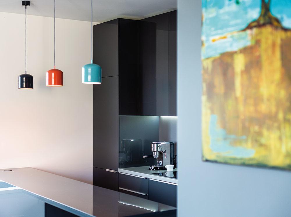 Trochu hravosti do interiéru prinášajú svietidlá vo veselej oranžovej atyrkysovej farbe, rovnako ako taburetky či farebný obraz nad plynovým krbom. Vďaka nim byt nepôsobí ponuro či smutne, ale prívetivo.