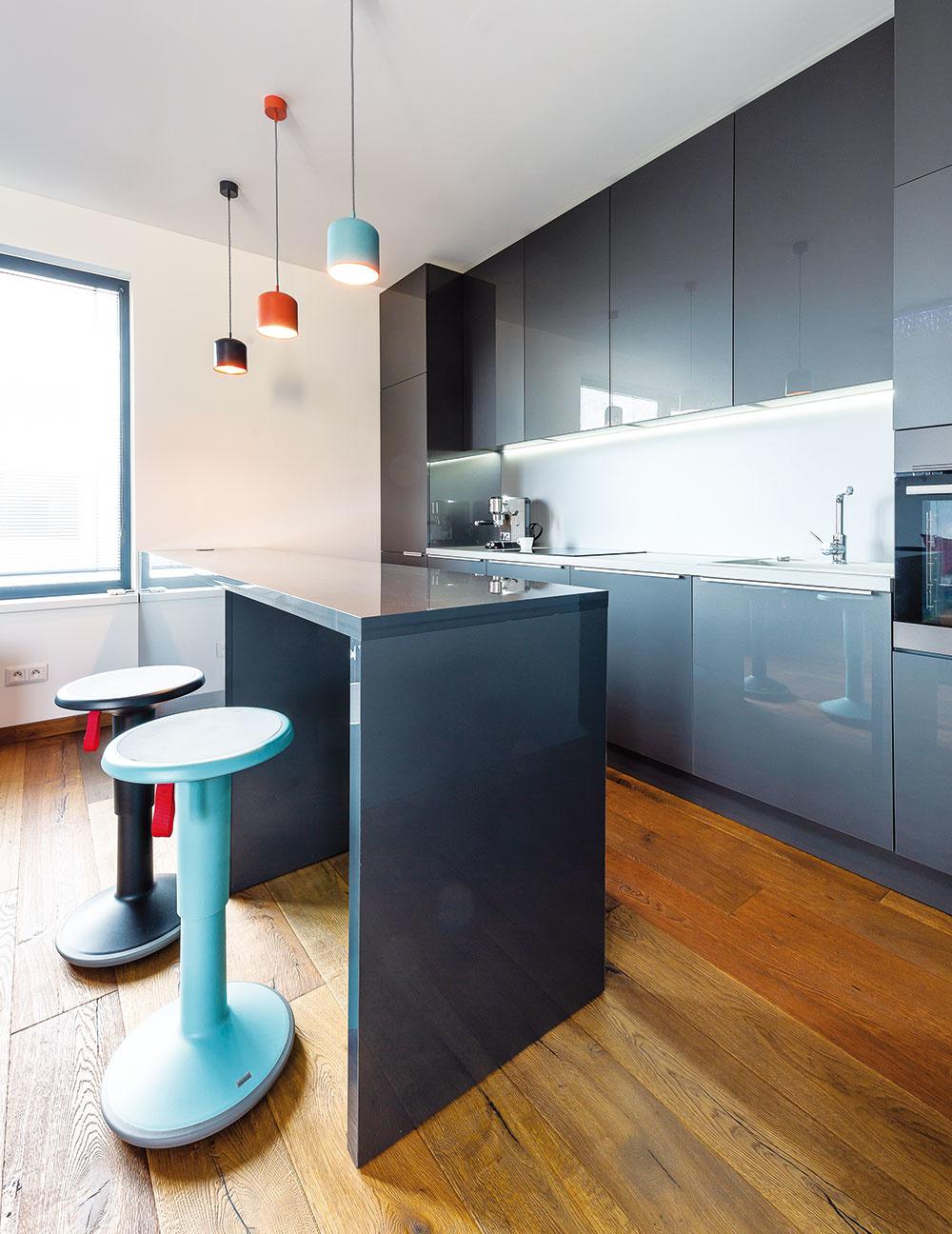 Vo večerných hodinách vytvárajú závesné svietidlá aj podsvietená kuchynská linka príjemnú atmosféru aopticky odčleňujú kuchyňu od obývacej časti.