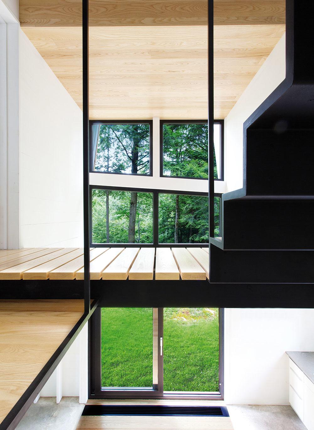 V MENE SVETLA. Aby bol v chate dostatok denného svetla, nenájdete v nej priveľa stien. Namiesto krytej chodby je preto na poschodí  len drevená lávka, ktorá vedie zo schodiska do izby.
