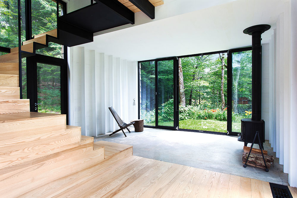 Žiarivé farby ani iné výstrednosti vnútri nenájdete. Interiér je kombináciou bielej, dreva ačiernych kovových prvkov. Farebnosť priestoru dodáva okolitá príroda, meniaca sa skaždým ročným obdobím.