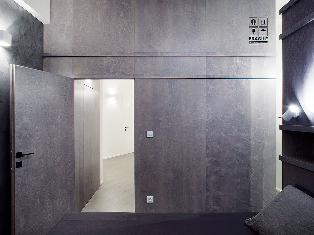 Drevené obloženie steny spálne evokuje farbou idekoratívnou potlačou prepravné kontajnery, ktoré sú pripomienkou pôvodného využitia celého objektu. Za obkladom je technická miestnosť spráčkou isušičkou ačasť šatníka.