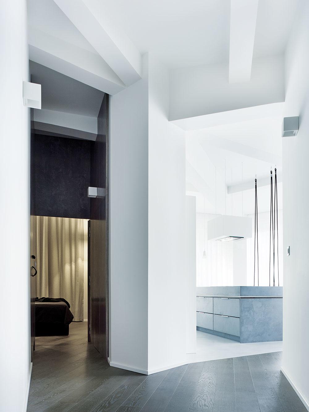 Nepravidelný tvar bytu je čitateľný už pri pohľade zchodby. Geometriu stavby zdôrazňujú betónové stropné nosníky, lúčovito vybiehajúce zmohutného centrálneho stĺpa.
