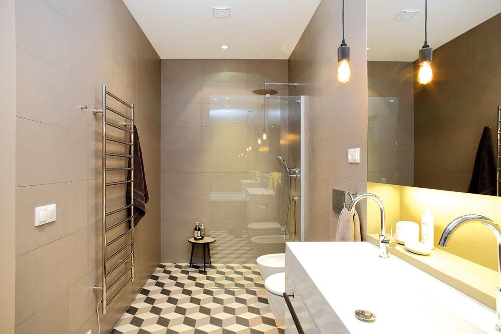 Kúpeľniam vládnu prírodné tóny aveľkoformátový obklad. Vďaka veľkým zrkadlám, vhodnému osvetleniu apohodlnému sprchovaciemu kútu, ktorý opticky neuberá zpriestoru, pôsobí aj úzka miestnosť priestranne.