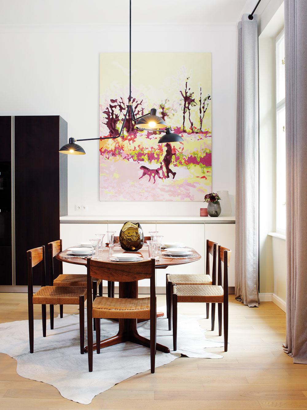 Rafinovaná kombinácia. Hoci základ interiéru tvorí kombinácia sivej, antracitovej aprírodného dreva, vhodne zvolené solitéry adoplnky vpastelových farbách, ku ktorým patrí aj výrazný obraz nad jedálenským stolom, dodávajú bytu hravosť aoptimizmus.