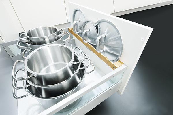 UKRYTÉ POKRIEVKY. Jednoduché riešenie, ktoré sa dá aplikovať do takmer každej kuchyne. Do šuplíka, vktorom máte uložené hrnce, si namontujte lištu, ktorá bude slúžiť ako odkladací priestor na pokrievky. Achaosu všuplíku je tým pádom koniec.