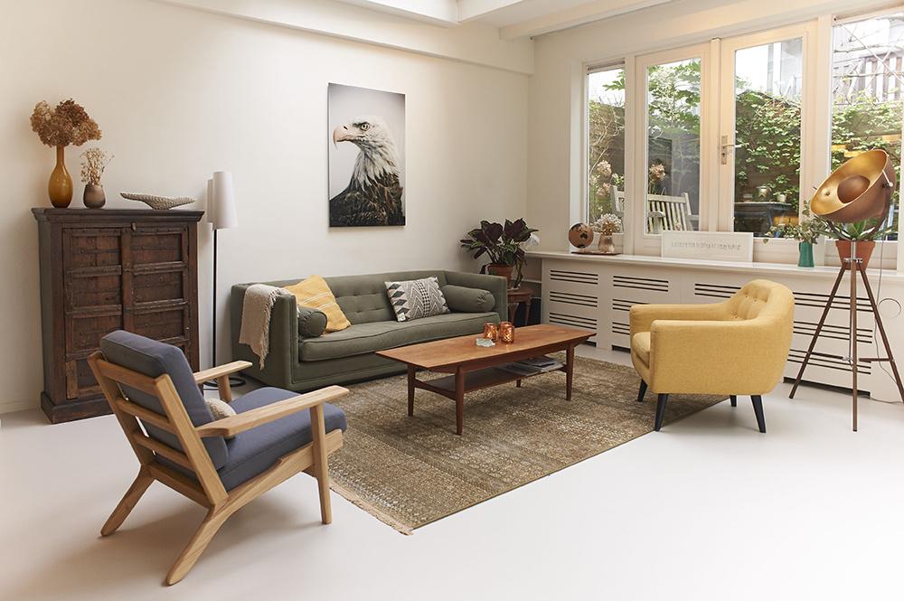"""Obývačka v retro štýle. Vystačí si s gaučom, dvoma rôznymi kreslami a """"vychodeným"""" kobercom. To všetko dopĺňa starožitný odkladací stolík v rohu a dve stojace originálne svietidlá."""