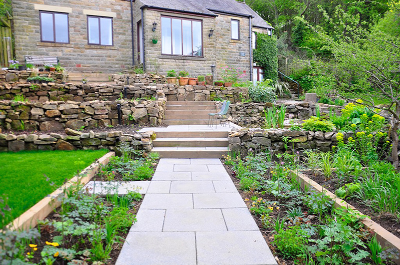 Pôvodné rastliny danej lokality si nevyžadujú žiadnu zvláštnu starostlivosť. V dažďovej záhrade vytvárajú nádherné kvetinové záhony bez prihnojovania či pesticídov. (Na obrázku je dažďová záhrada v prvom roku výsadby. Autorom návrhu je jeden z priekopníkov bioretenčných systémov Nigel Dunnett.)