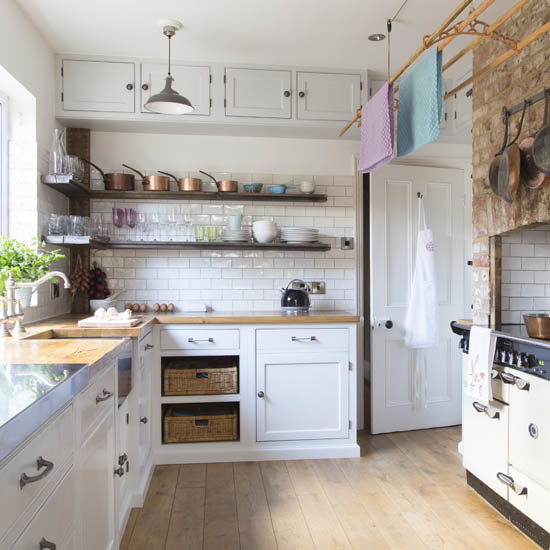 Rustic, country style kitchen, vintage range cooker inside hollowed out brick wall, white fitted untis, tiled walls, fitted metallic shelves, natural wood plank flooring.