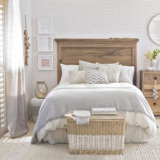 Fish-print wallpaper on feature wall, bedroom, wooden bedstead and matching chest of drawers, coastal motifs, neutral beige sisal carpet, wicker basket, Pub Orig