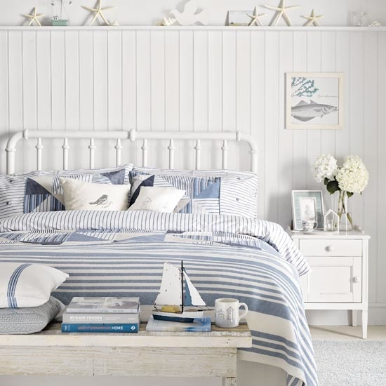 White bedroom with coastal theme, tongue and groove panelled walls, blue and white striped bedding, distressed wooden table, starfish and shells, IH 08/2013 Pub Orig