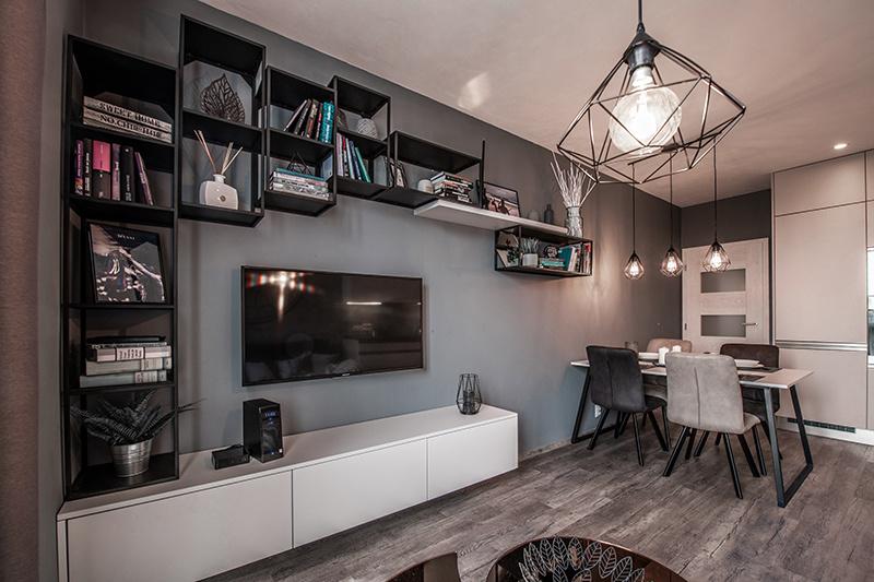 Kovové regály pokračujú až k jedálenskému stolu a poskytujú dostatok úložného priestoru na knihy a dekoračné predmety.