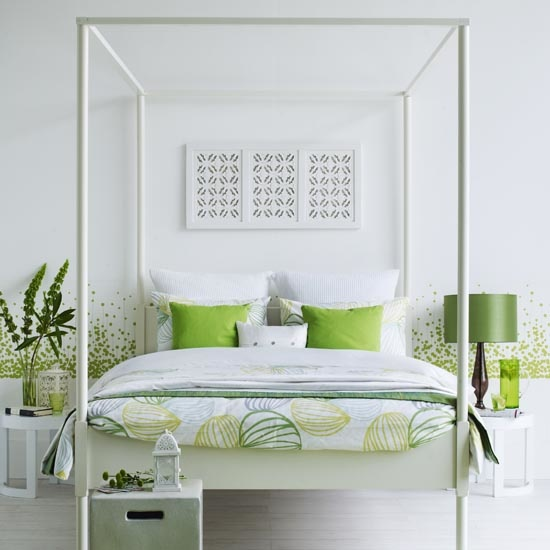 White and green bedroom, white four poster bed, geometric print bed covers, green cushions, green rug, cut out wood wall art, small table at end of bed. IH 08/2010 Pub orig