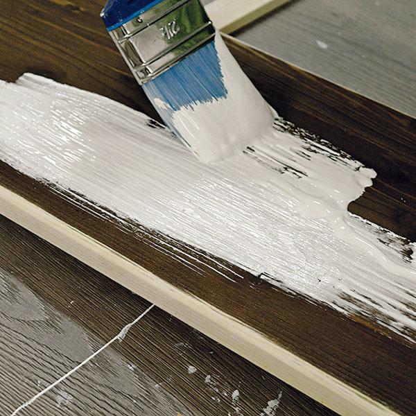 Prednú stranu dvierok obrúsenú kefovou brúskou natrite štetcom vrstvou základnej bielej farby.