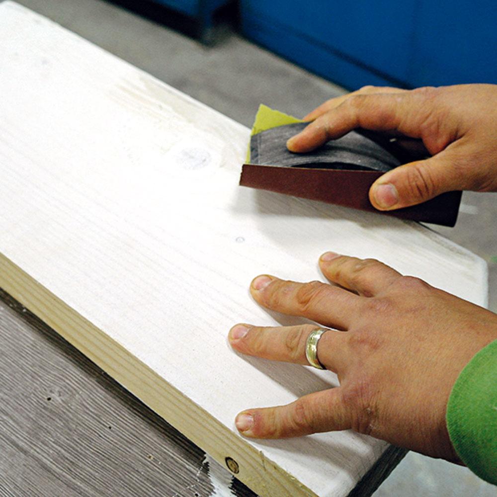Po zaschnutí bielej základovej farby ju prebrúste brúsnym papierom, aby ste odstránili vystúpené vlásočnice dreva.
