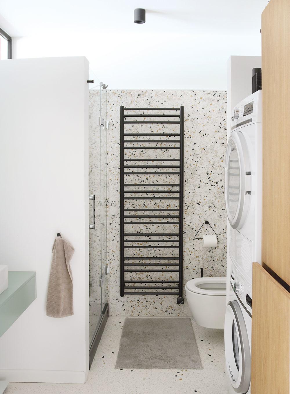 Kúpeľňu vo vstupnej časti bytu jednak zväčšili, jednak znížili na úroveň podlahy vhale. Pôvodná kúpeľňa bola totiž celá na nezmyselnom stupienku. Vnovej vyriešili odpad zo sprchovacieho kúta len vrámci zvýšenej vaničky. Aj tu nechali naplno vyniknúť zaujímavý materiál – terazzo.