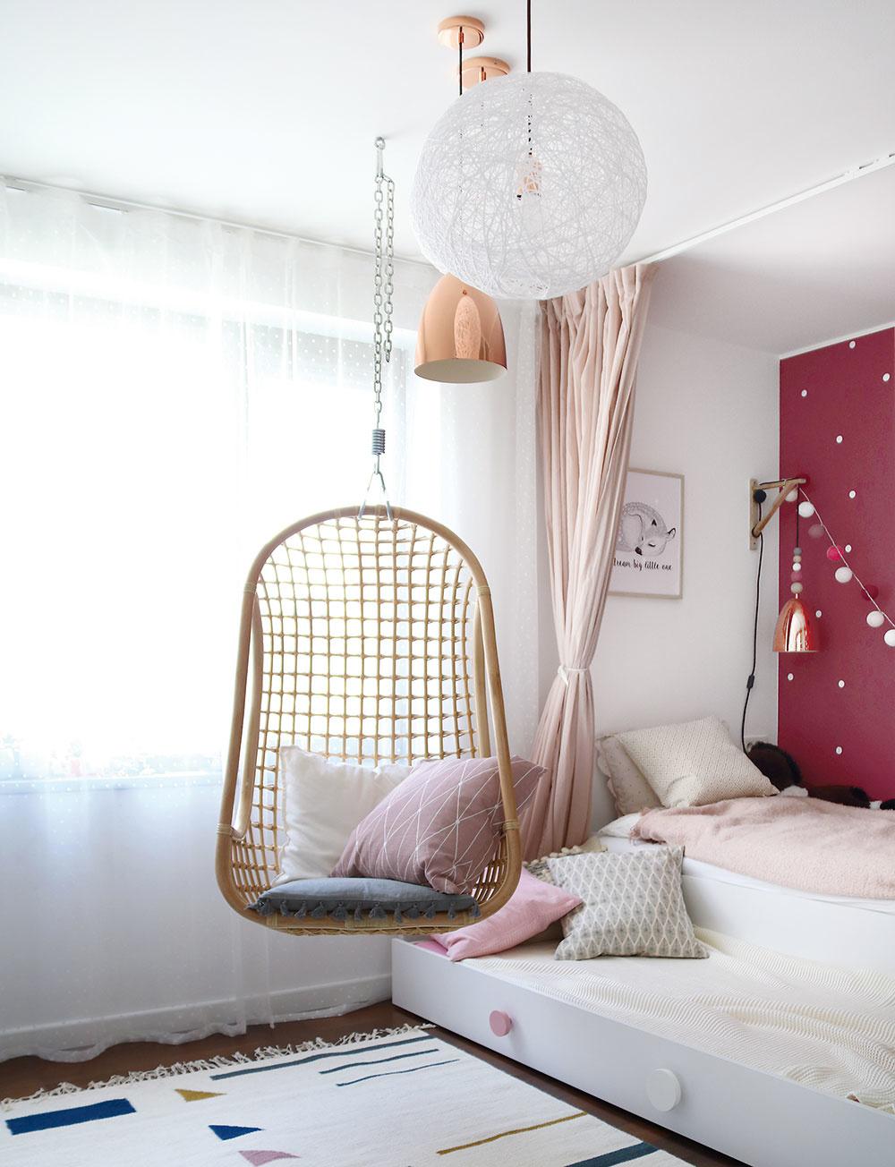 """Vdievčenskej izbe dopĺňa biely nábytok tmavoružová farba dominantnej steny za posteľou. Na posteli """"so šuplíkom"""" je dosť miesta aj pre kamarátku, nežné """"pavučinkové lampy"""" anočnú lampu sem vyrobili Lucie."""