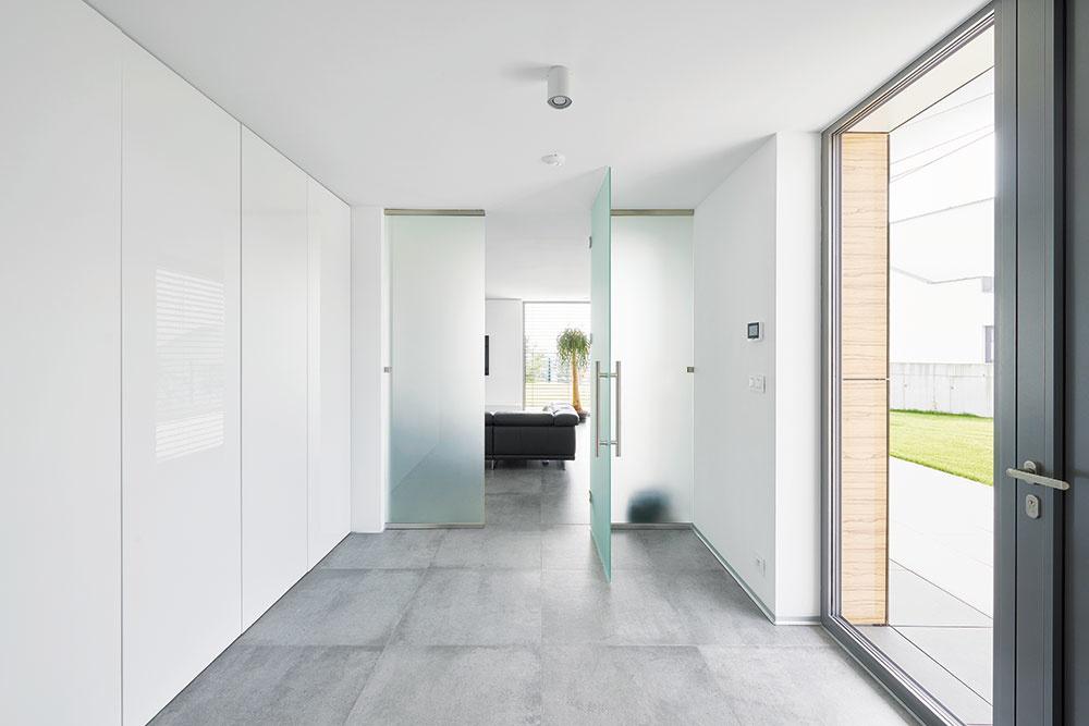 Bez zbytočností. Už vstupný priestor, pôsobiaci veľmi čisto, naznačuje minimalistický štýl, vakom sa nesie celý interiér. Biele steny aveľké plochy skla dopĺňa sivá dlažba, ktorá plynule prechádza do spoločenského centra domu. Zohľadnila sa tu taktiež dôležitá požiadavka majiteľov na štedro riešené úložné priestory.
