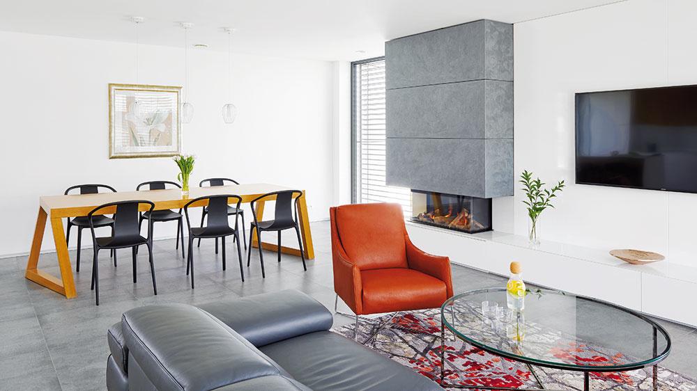"""Jedálenský stôl aostatné nosné prvky interiéru vybrali architekti spoločne smajiteľom, rovnako aj veľkoformátovú dlažbu sbetónovou textúrou. """"Vďaka jej tmavému odtieňu vynikne dominanta obytného priestoru – jedálenský stôl sasymetrickými nohami,"""" vysvetľuje Miroslav Prešinský."""