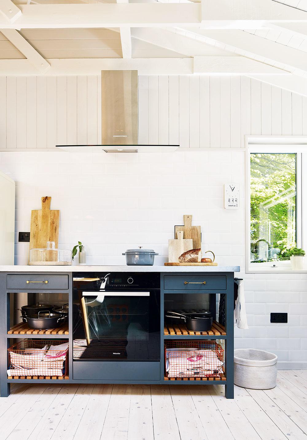 """Voľne stojace skrinky odľahčujú zariadenie kuchyne aposúvajú jej vidiecky vzhľad do modernejšieho štýlu. Drevený obklad striedajú vokolí pracovných plôch praktickejšie biele obkladačky, uložené vduchu dnešného trendu """"na väzbu""""."""