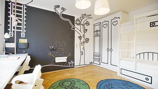 Tabuľovú stenu pri písacom stole používajú deti na kresby ijednoduché odkazy. Nábytok vyrobený na mieru optimálne využil priestor vmalej izbičke.