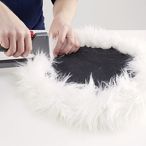 Zošívačkou pripevníme kožušinu na sedadlo. Môžete použiť klinčeky či pripináčiky.