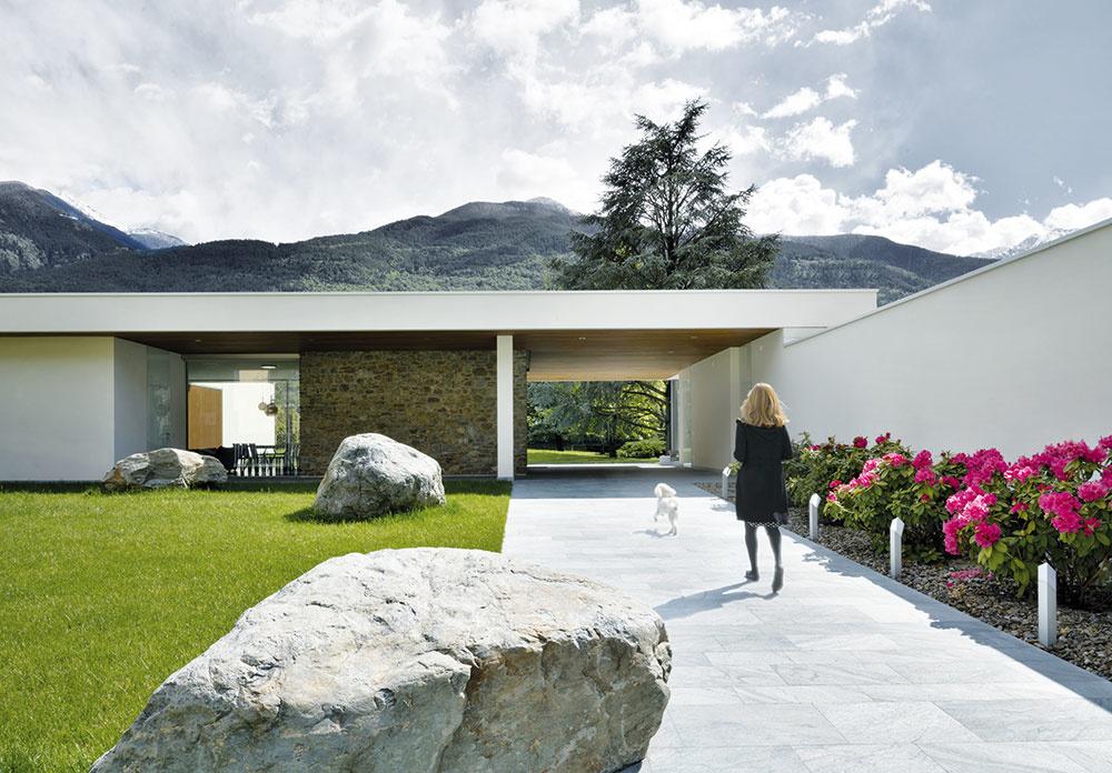 Prístupový chodník je zároveň kompozičnou osou, ktorá člení rozľahlú stavbu na dve časti – vpravo za múrom lemovaným rododendronmi je garáž apriestor pre hostí, vľavo sa rozprestiera rezidencia majiteľov. Kryté patio, ktoré ich prepája, sa využíva aj ako vonkajšia jedáleň.