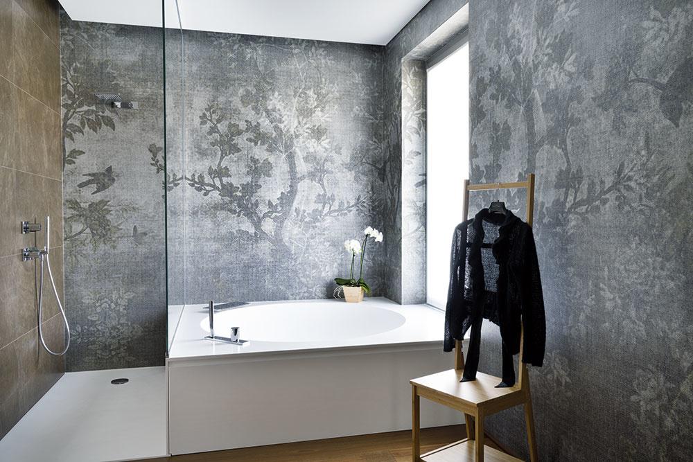 Striebrosivé tapety sdecentnými prírodnými motívmi dodávajú kúpeľniam atmosféru luxusu. Aj pre tieto priestory je typická kombinácia tmavého olejovaného dreva sčiernou abielou, ktorá charakterizuje celý dom.