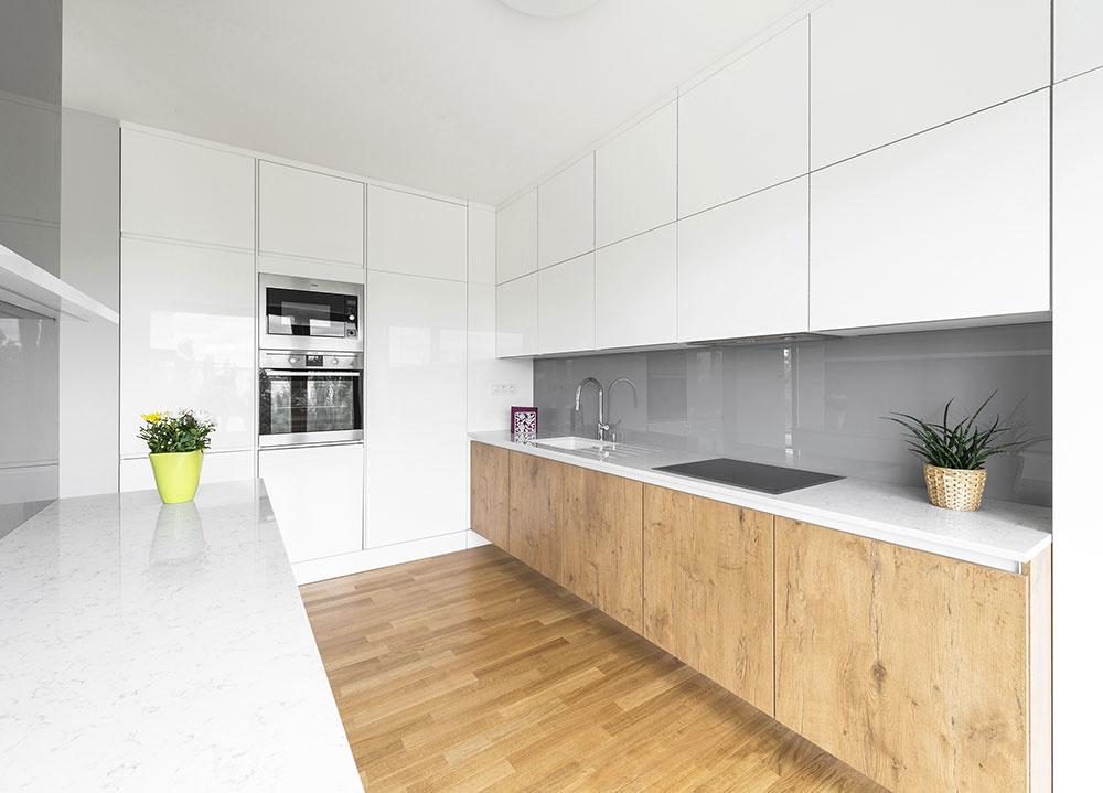 Architekti navrhli skrinky od podlahy k stropu. Biele dvierka vo vysokom lesku sú kombinované s dvierkami v dekore s výraznou kresbou dreva.