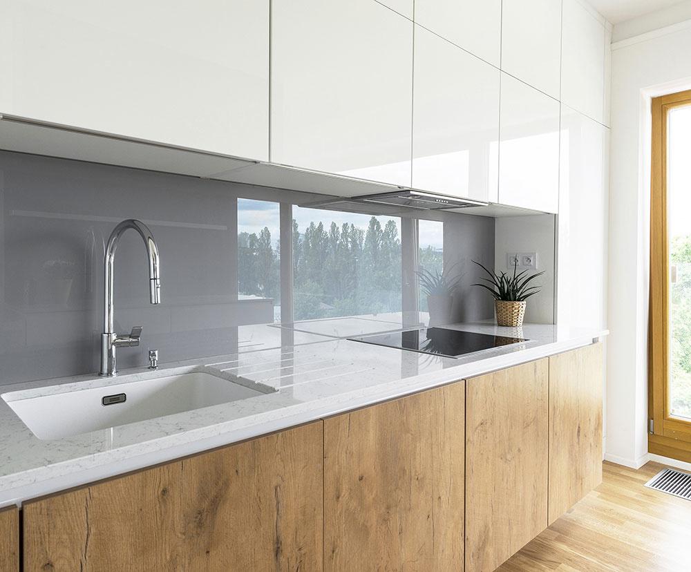 Riešenie podľa aktuálnych módnych trendov, biely vysoký lesk, sivé sklo na zadnej stene a spodné skrinky v dekore dreva.