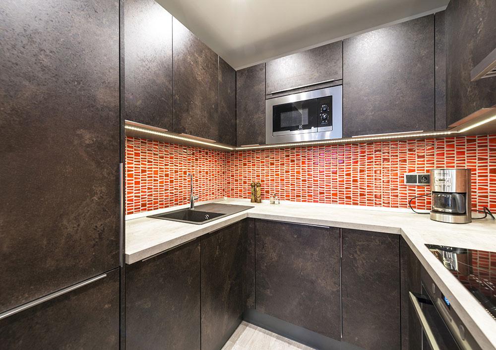 Povrch kuchyne má jemnú štruktúru, do svetlej pracovnej dosky je osadený fragranitový drez v antracitovej farbe, nechýba ani vstavaná mikrovlnná rúra.
